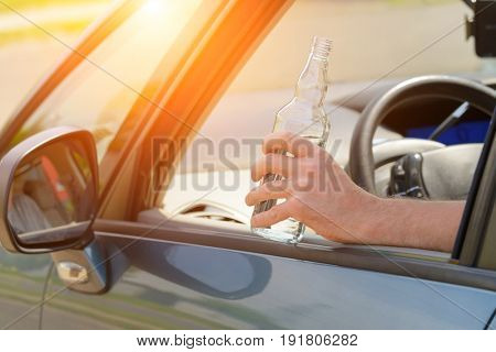 Man holding bottle of alcohol in hand while driving a car. Don't drink and drive concept