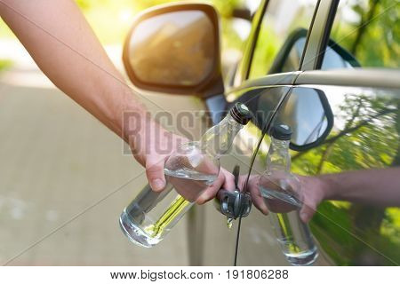 Man opening his car while holding a bottle of alcohol. Don't drink and drive concept