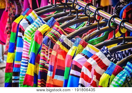 Colorful Pants hanging on a rack in a market store.
