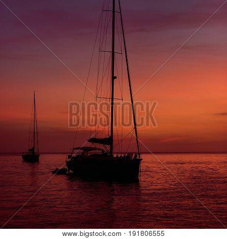 Yacht at Cala Saona in Formentera during the colorful sunset. Idyllic scenery. Balearic Islands. Spain