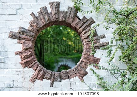A round hole in a brick wall in a park looks like a portal to another dimension