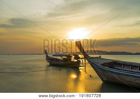 Traditional long-tail boat on the beach in Krabi Thailand at sunset