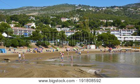ALCOSSEBRE, SPAIN - JUNE 12, 2017: People enjoying the warm weather at Las Fuentes beach in Alcossebre, in the Costa del Azahar, Spain