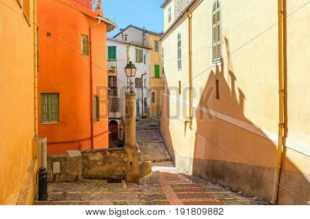 Narrow street among colorful houses in old town of Menton, France.