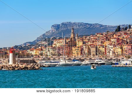 Yachts in harbor and old colorful houses of Menton on background  on French Riviera.