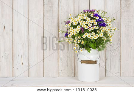 Wild chamomile flowers bouquet on table over wooden planks background