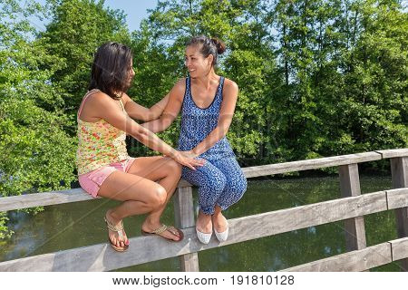 Two young women sitting together on bridge railing in nature