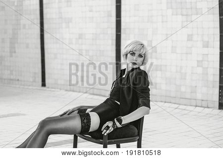 monochrome portrait of beautiful young blonde sensual woman in black underwear and stockings alone in the empty swimming pool
