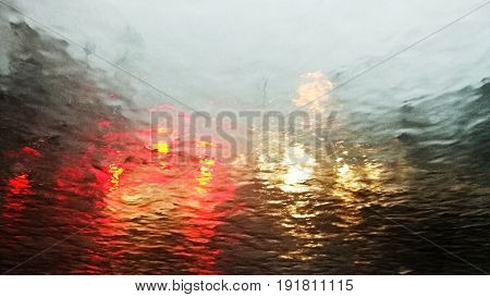 Heavy rain on car window. Abstract blur of car light with traffic jam