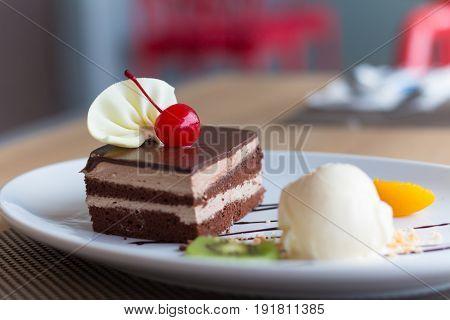 chocolate layer cake and vanilla ice cream with fresh fruit and cherry