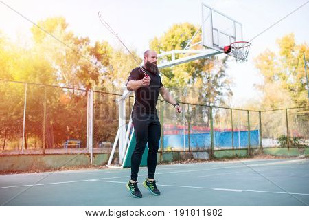 Side View Of Bearded Sportsman Jumping With Skipping Rope On Stadium
