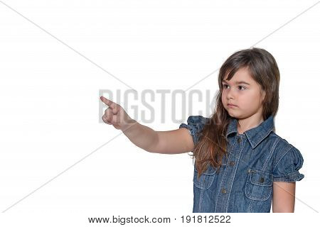 Little girl with a serious expression on her face is pointing index finger into space. All is isolated on the white background.