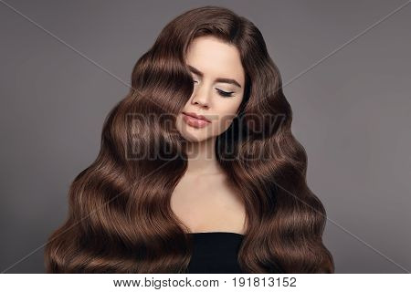 Healthy hair. Brunette girl portrait with long shiny wavy hair. Beautiful model with curly hairstyle and eyeliner makeup isolated on studio dark background.