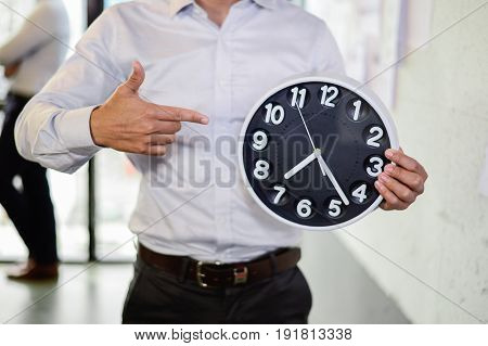 serious businessman holding big clock in his hands, Time to work. time to start
