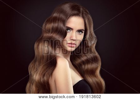 Healthy hair. Brunette girl portrait with long shiny wavy hair. Beautiful model with curly hairstyle and eyeliner makeup isolated on studio black background.