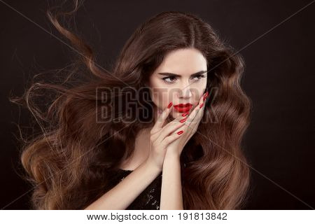 Beauty hair. Red manicure. Brunette girl with long shiny wavy hair. Beautiful model portrait with curly hairstyle and manicured nails isolated on studio dark background.