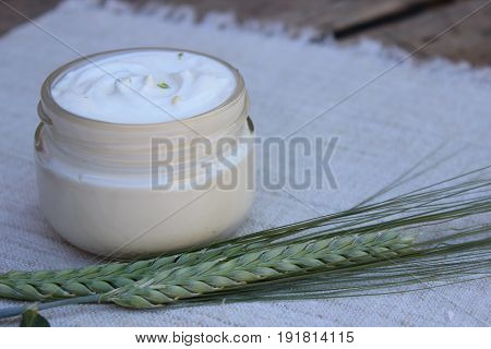 Organic cosmetic cream with wheat spike on the background of flax
