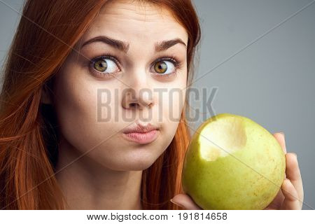 Diet, vitamins A, B, C woman eating an apple, a woman took a bite of an apple and acer portrait background.
