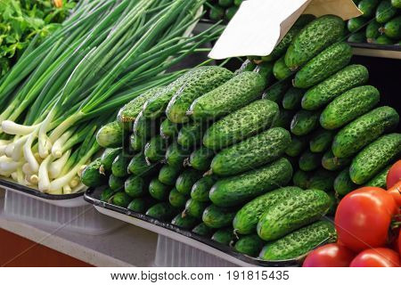 cucumbers, spring onions and fresh tomatoes on farmer's market vegetable stand.