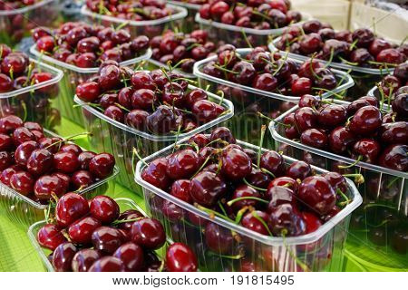 cherries in baskets on farmer's market stand.