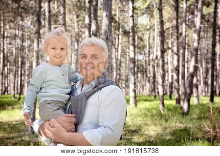 Happy senior man with granddaughter in forest on sunny day