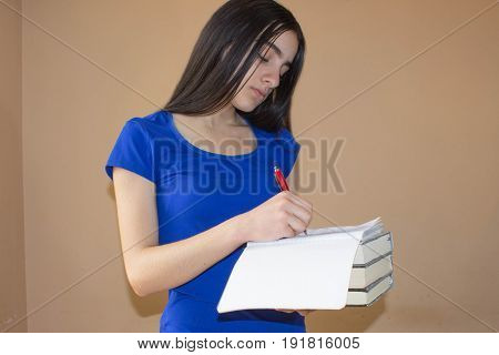 Young Girl and writing information she has found in a large book into her notebook. Education concept