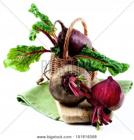 Two Fresh Raw Organic Beet Roots with Green Beet Tops and One Half in Wicker Basket on Wooden Board and Napkin isolated on White background
