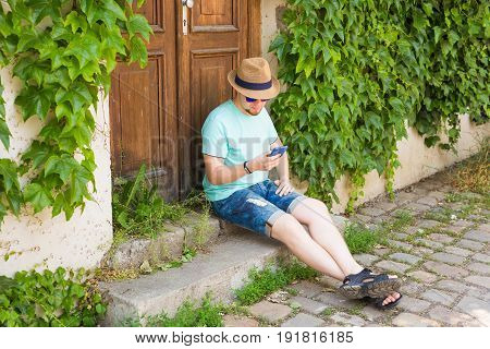 Young hipster man using mobile smart phone.
