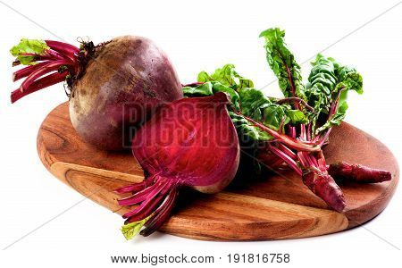 Arrangement of Full Body Half and Young Sprouts of Fresh Raw Organic Beet Roots with Green Beet Tops on Wooden Cutting Board isolated on White background