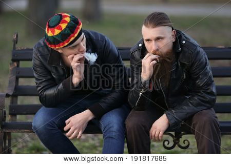 Two men smoking weed while sitting on bench outdoors
