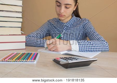 School books and pencils on desk education concept. Girl doing lessons at home