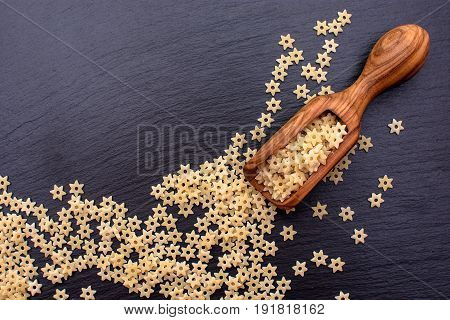 Pasta In The Form Of Asterisks Lie In A Wooden Spoon On A Black Stone Board, Space For Text