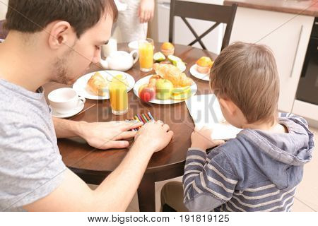 Young man with son drawing on kitchen table