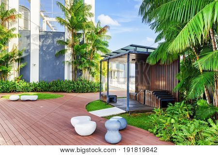 Beautiful rooftop garden. Outside terrace with amazing park. Modern wooden arbor among green trees. Urban eco design and mini-ecosystem. Landscaping in Singapore. poster