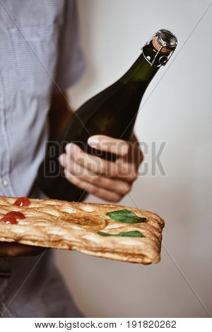 closeup of a young caucasian man with a bottle of champagne and a coca de Sant Joan, a typical sweet flat cake from Catalonia, Spain, eaten on Saint Johns Eve