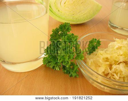 Sauerkraut juice in glass and sauerkraut in bowl