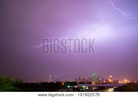 The sky is lit up purple over Dallas during a summer thunderstorm