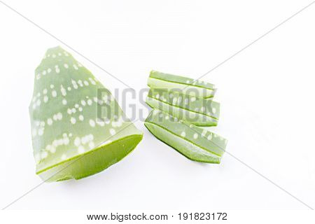 Leaf of sabila with three sections cut to the side on a white background.
