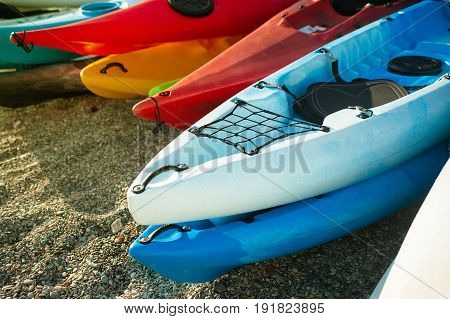 colorful of kayaks boat on the beach. Kayak on the Rocky Lake Shore.