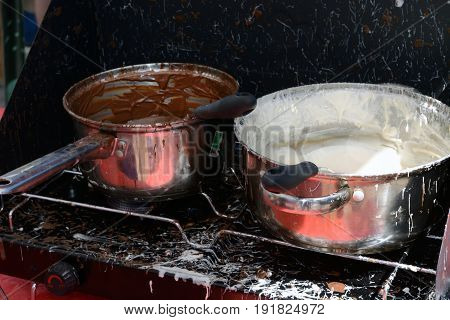 Pots of melted milk chocolate and white chocolate on outdoor stove for making dessert topping at farmer's market