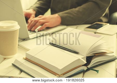 Open notepad with black pen on work-table. Paper cup of coffee, office stuff, laptop and working man on background, horizontal, toned
