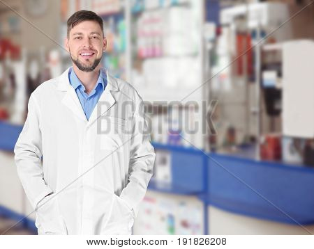 Male pharmacist at work. Blurred shelves with pharmaceutical products on background