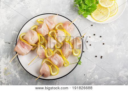 Chicken kebab on skewers with lemon before preparation. Top view