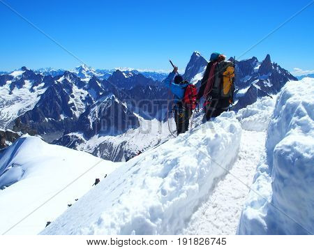 Two alpinists and mountaineer climber on AIGUILLE DU MIDI CHAMONIX MONT BLANC french ALPS top alpine mountains range landscape FRANCE with clear blue sky in 2016 warm sunny summer day Europe on July.