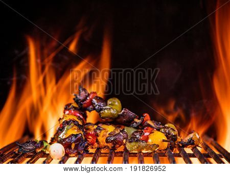 Tasty chicken skewers on the grill with fire flames