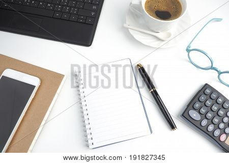 Blank page notebook on white desktop with pen coffee laptop book calculator glasses and mobile phone top view, business desktop