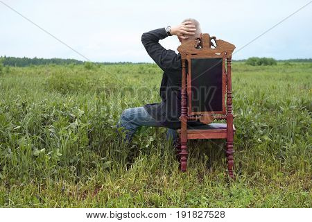 Man having a rest sitting in carved wooden chair back view outdoor photo