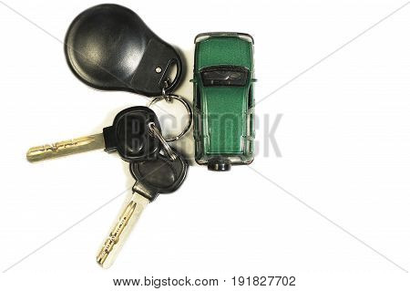Toy car and car keys isolate, on white background two keys with remote control and a dark green toy car