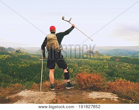 Wounded Tourist With Crutch Above Head Achieved Mountain Peak. Hiker With  Knee Brace Feature.