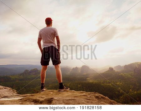 Tall Man Enjoy Freedom On Peak Of Mountain Edge. Alone Tourist  Watching Over Misty Valley